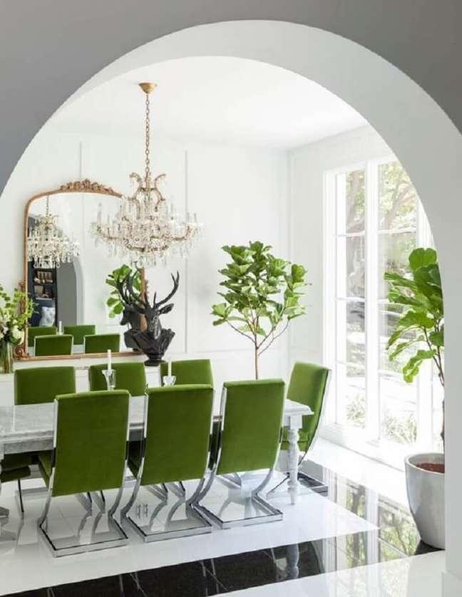 52. Sala branca decorada com lustre de cristal e cadeira de jantar verde – Foto: Pinterest