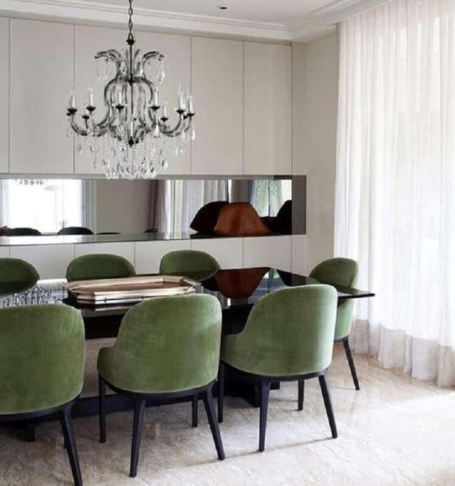 42. Decoração de sala de jantar com lustre de cristal e cadeira verde musgo – Foto: Jeito de Casa