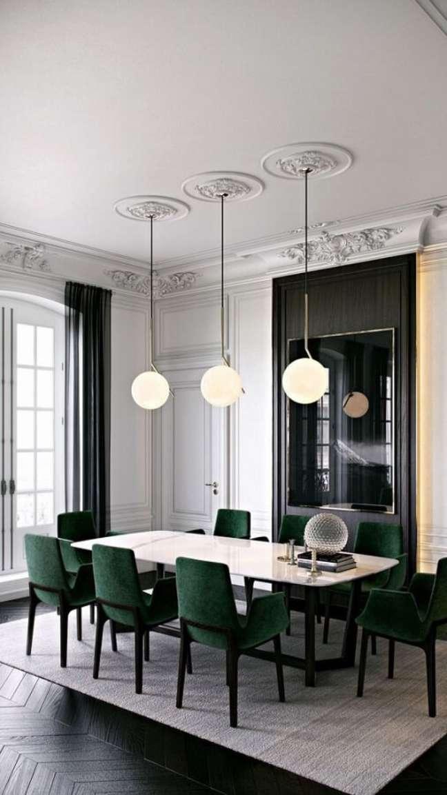 44. Decoração de sala de jantar sofisticada com luminária moderna e cadeira verde escuro – Foto: Apartment Therapy
