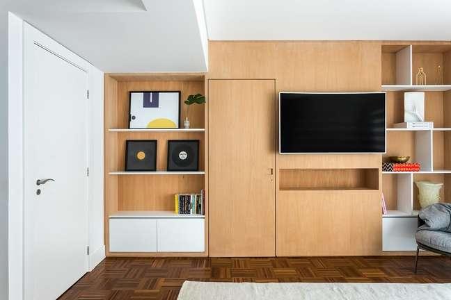 10. O painel com nichos da TV foi desenhado incorporando a porta do closet ao conjunto. Foto: Eduardo Macarios