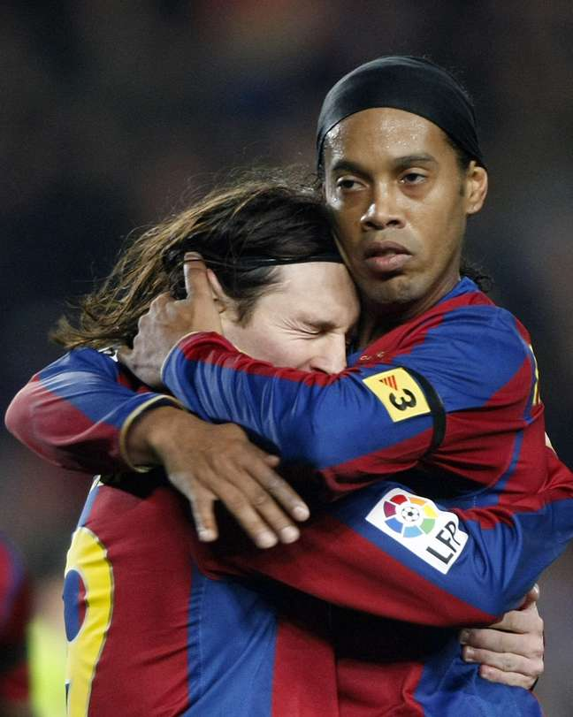 Ronaldinho abraça Messi na época em que defendiam o Barcelona