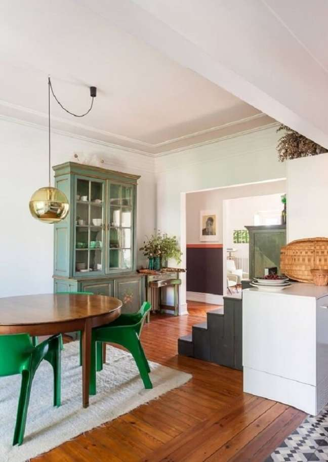 26. Cadeira verde moderna para sala de jantar decorada com mesa de madeira e luminária redonda – Foto: Histórias de Casa