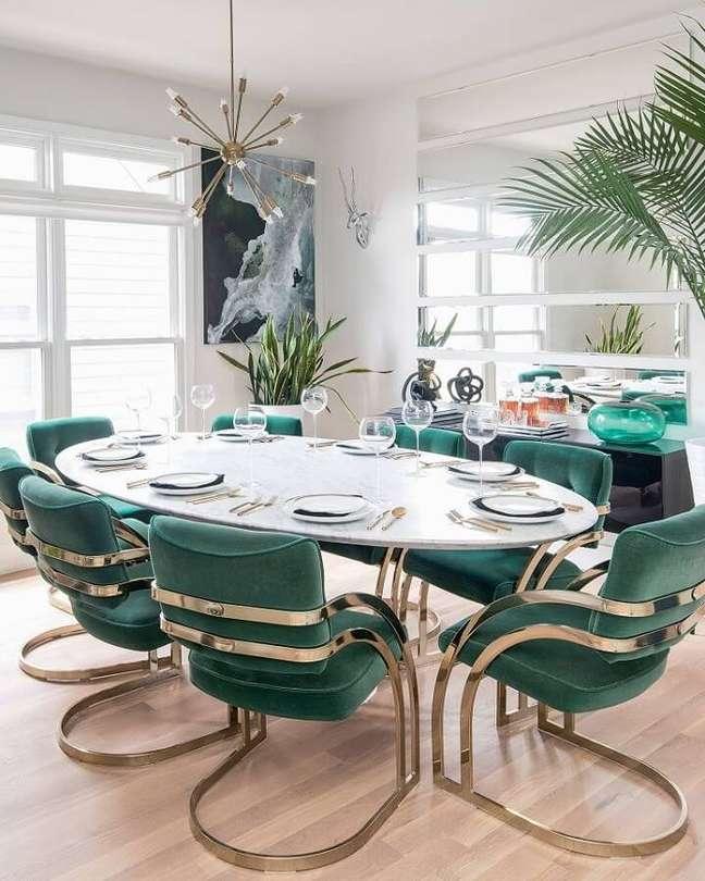 43. Decoração de sala de jantar com mesa oval e cadeira verde moderna estofada – Foto: Apartment Therapy
