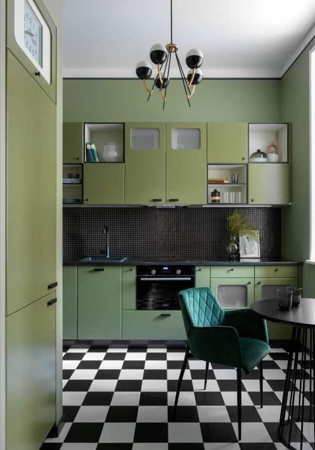 33. Cozinha retrô decorada com piso preto e branco e cadeira estofada verde escuro – Foto: Decoist