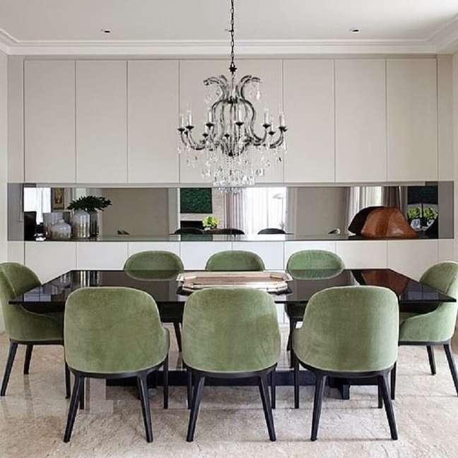 28. Cadeira verde musgo para sala de jantar moderna decorada com lustre de cristal – Foto: Jeito de Casa