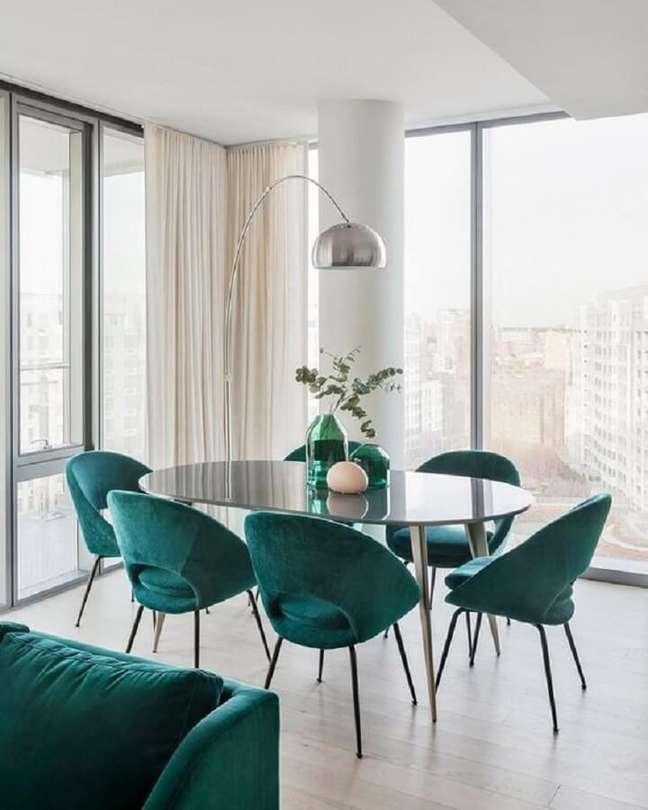 37. Decoração clean para sala de jantar com mesa oval preta e cadeira estofada verde – Foto: Curated Interior