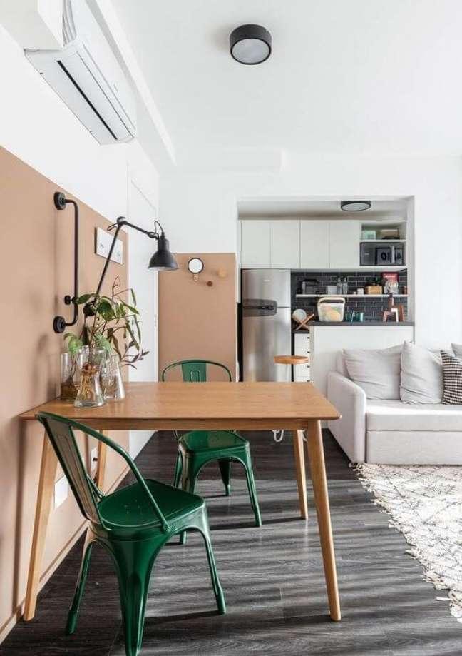 49. Mesa de madeira e cadeira verde escuro para decoração de sala de jantar pequena integrada com sala de estar – Foto: Histórias de Casa
