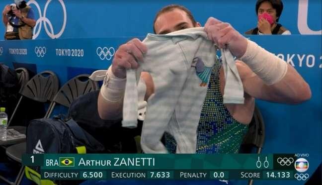 Zanetti mostra o 'amuleto' durante os Jogos, uma roupinha do filho Liam (Foto: Reprodução/Globo)