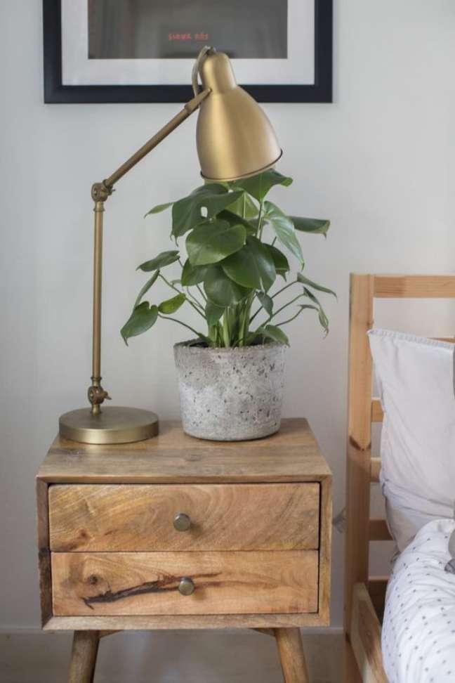 17. Mesa de cabeceira retrô de madeira com luminária e vaso de planta – Foto Apartment Therapy