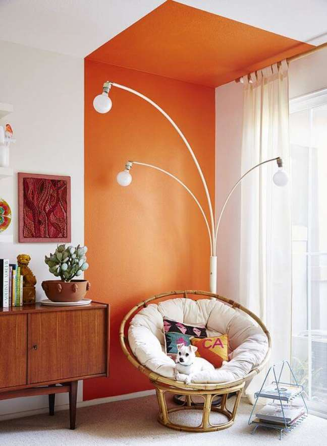 55. Parede de sala decorada com pintura setorizada laranja perto do rack de madeira e poltrona de ratan – Foto Pinterest