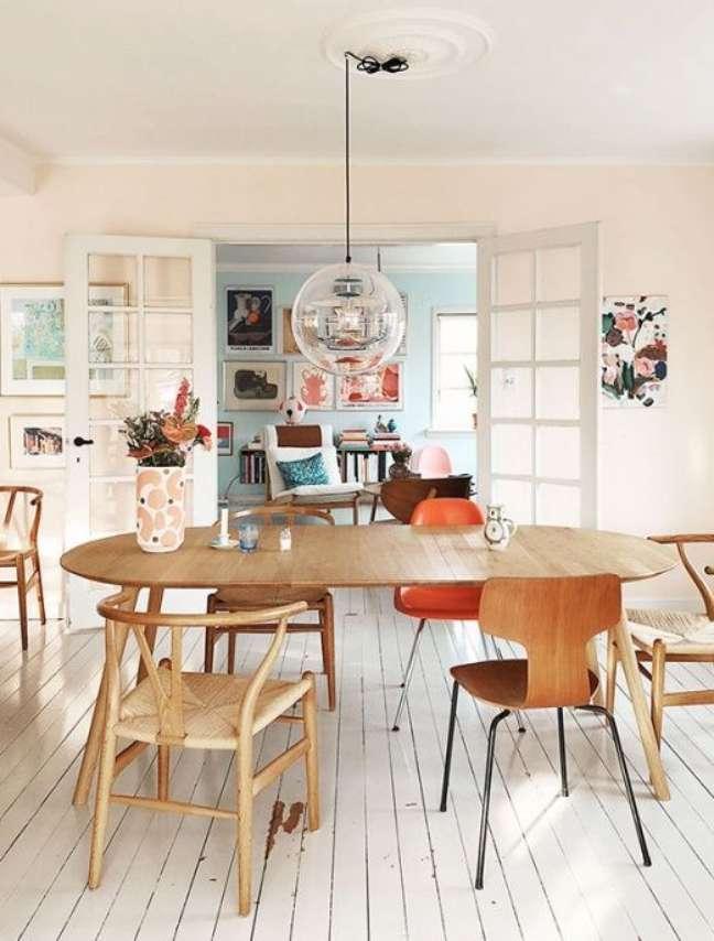 38. Mesa retrô de madeira no formato oval com cadeiras de diferentes tipos -Foto Pinterest