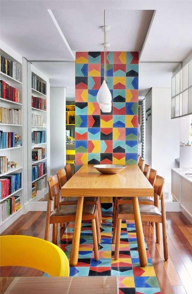 60. Sala de jantar com mesa retrô de madeira e azulejos coloridos na parede e chão – Foto Follow the Colours