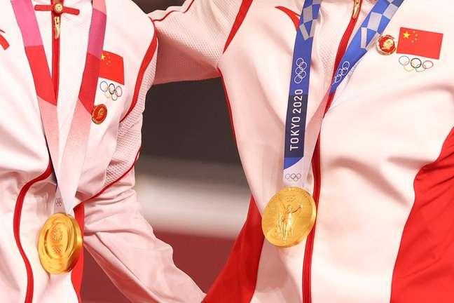 Emblemas de Mao Tsé Tung no uniforme das ciclistas chinesas Bao Shanju e Zhong Tianshi durante cerimônia de premiação em que receberam a medalha de ouro na Olimpíada de Tóquio 02/08/2021 REUTERS/Matthew Childs