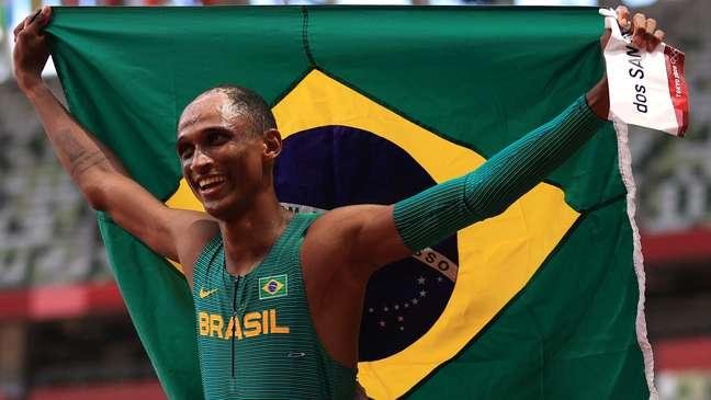 Alison dos Santos exibe a bandeira brasileira ao comemorar sua medalha de bronze