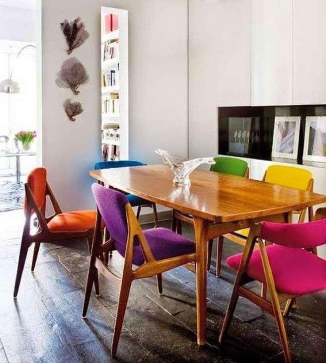 49. Sala de jantar com cadeira retrô colorida estofada de madeira na mesa de pés de palito – Foto FlavianMillen