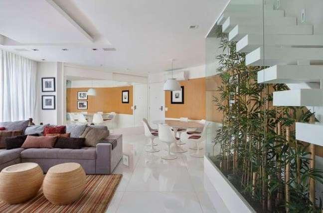 22. Cores de tinta para sala em tons de laranja com sofá cinza e decoração de madeira moderna – Foto Revista VD