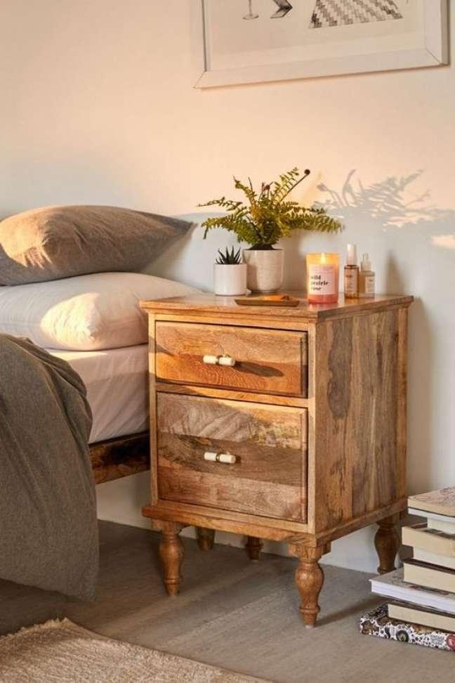 18. Mesa de cabeceira retrô de madeira com vaso de flores e vela -Foto PopSugar