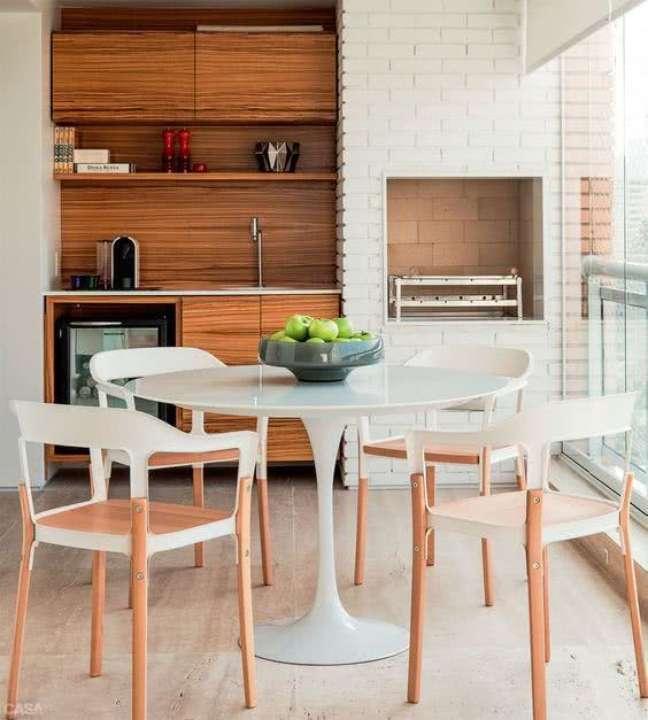 45. Varanda gourmet com mesa retrô branca e redonda com cadeiras do conjunto – Foto Pinterest