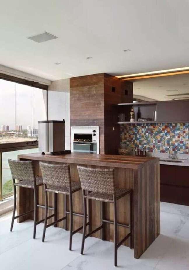 16. Bancada de madeira para decoração de apartamento com varanda gourmet e churrasqueira – Foto: Pinterest