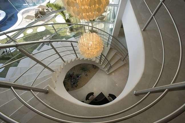 3. Invista em um lustre para escada pé direito alto e deixe o projeto ainda mais elegante. Projeto por Aquiles Nicolas Kílaris