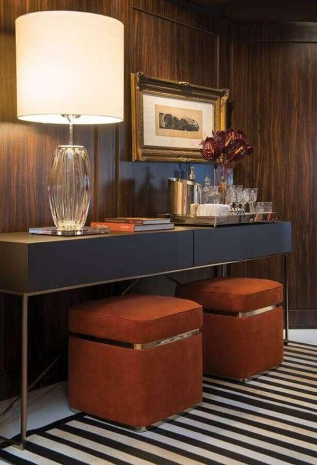 4. Corredor decorado com parede de madeira e puff banqueta quadrado embaixo de aparador – Foto: Habitare
