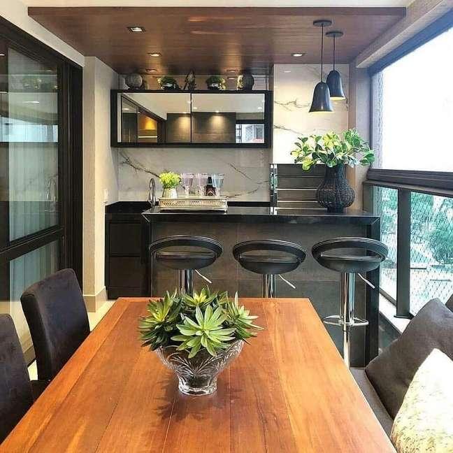 14. Apartamento com varanda gourmet e churrasqueira decorada com mesa de madeira e banqueta preta – Foto: Jeito de Casa