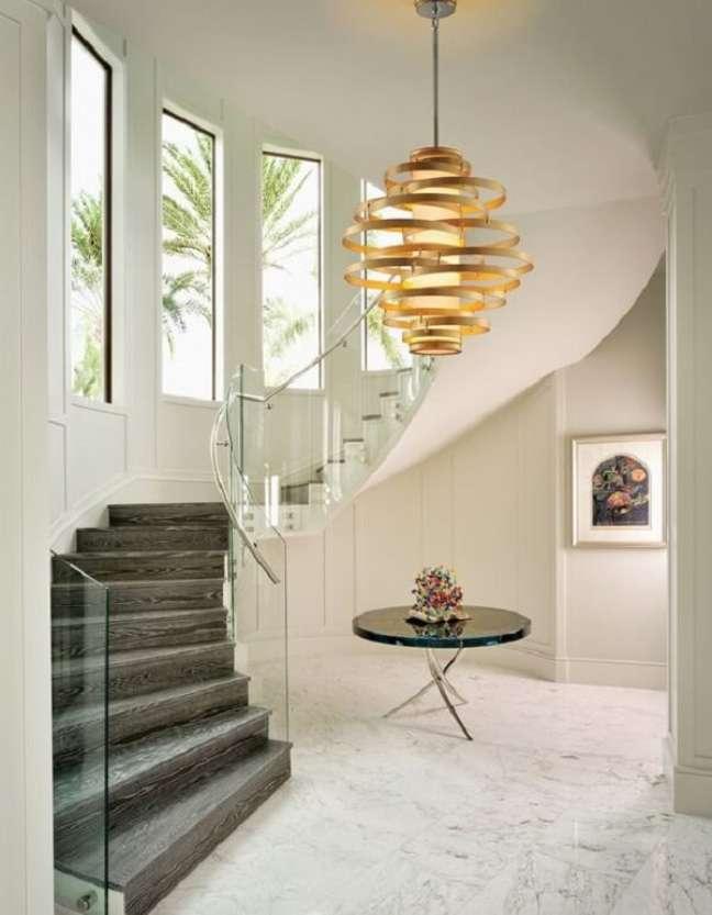24. Lustre pendente para escada com design dourado. Fonte: Pinterest