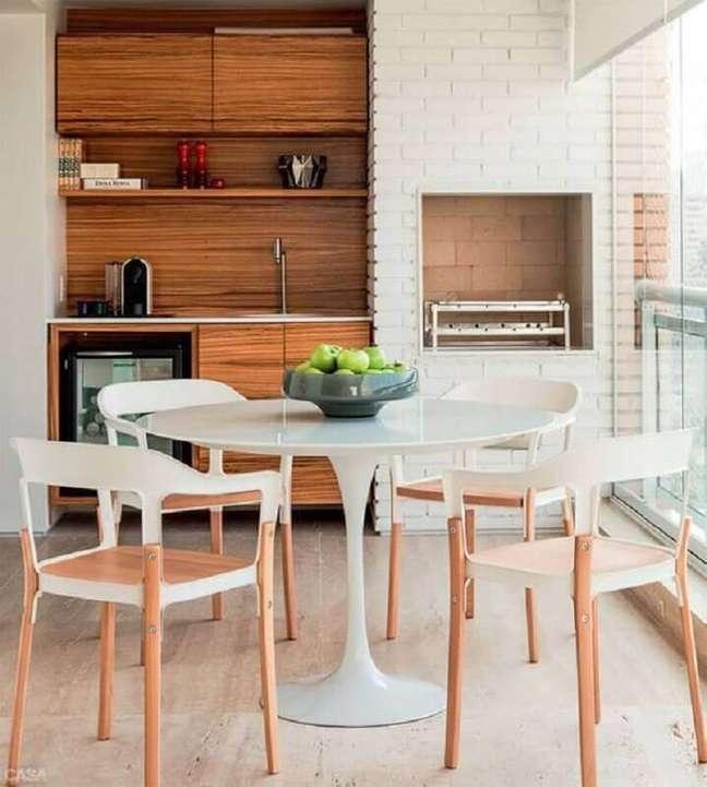 50. Mesa redonda para decoração de apartamento com varanda gourmet e churrasqueira – Foto: Arquitrecos