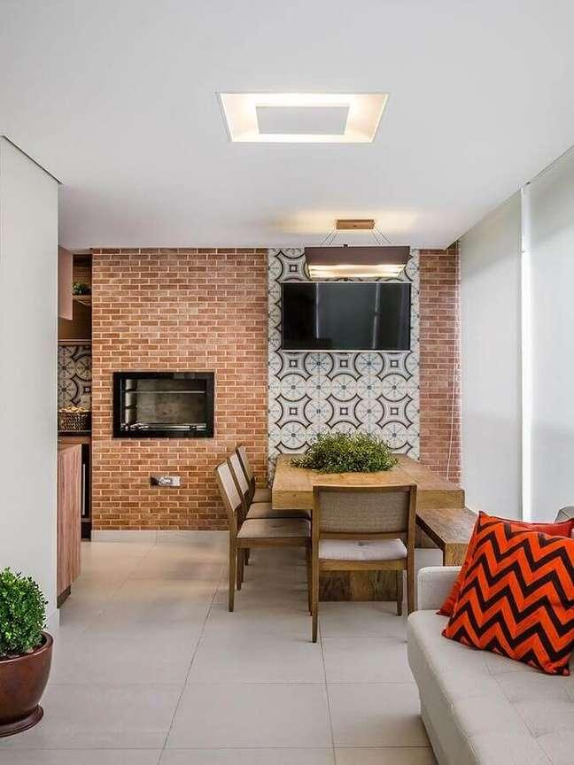 46. Mesa de madeira e parede de tijolinho à vista para decoração de apartamento com varanda gourmet – Foto: Mariana Lobo