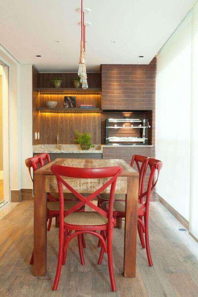 1. Apartamento com varanda gourmet decorado com cadeira vermelha para mesa de madeira rústica – Foto: Liliana Zenaro