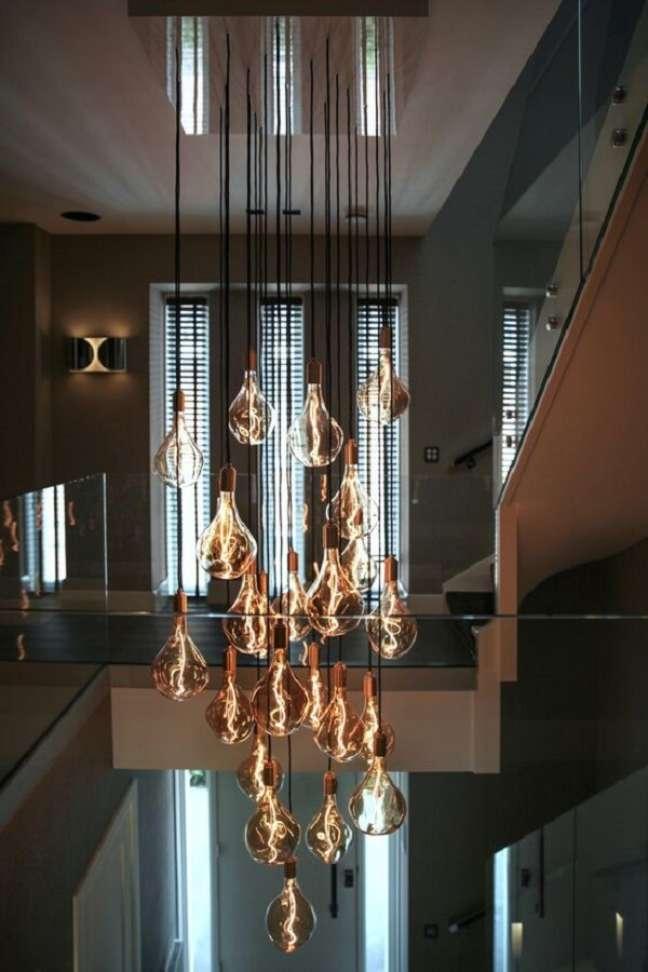 44. É difícil não se encantar pelos filamentos das lâmpadas desse lustre para escada. Fonte: Pinterest
