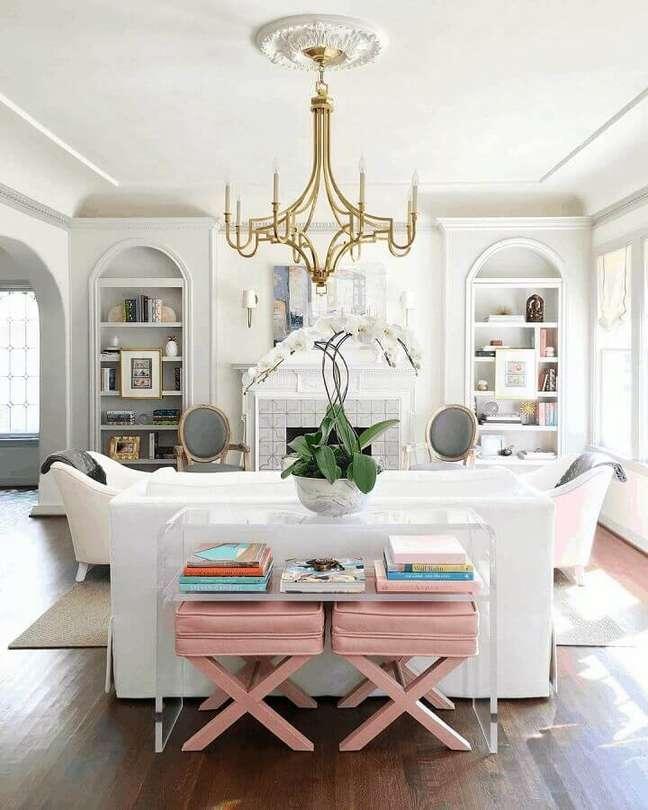 15. Decoração clássica para sala branca com banqueta puff rosa claro – Foto: Catherine French Design