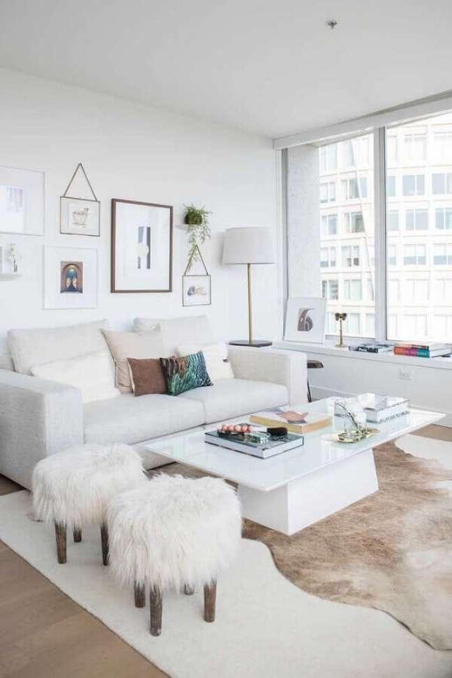 53. Sala de estar branca decorada com tapete de couro e puff banqueta redondo – Foto: Apartment Therapy
