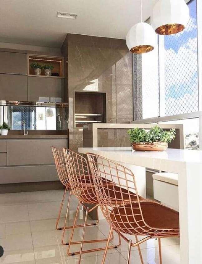 25. Cadeira rose gold para decoração de apartamento com varanda gourmet e churrasqueira – Foto: Jeito de Casa