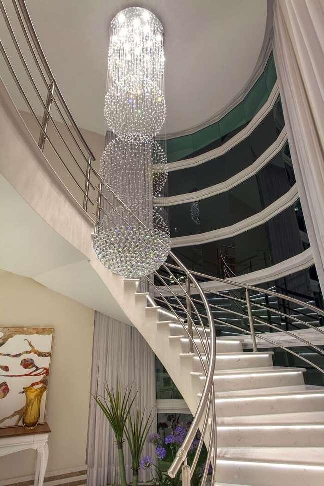 31. Lustre para escada pé direito alto repleto de cristais. Projeto de Iara Kilaris