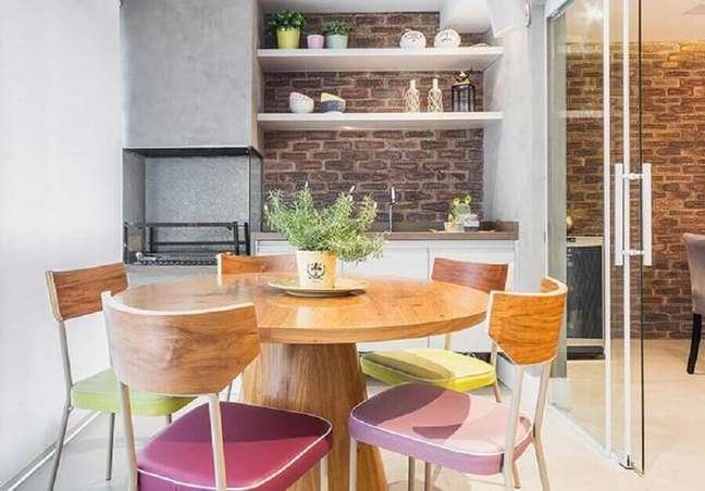 51. Mesa redonda para decoração de apartamento com varanda gourmet e churrasqueira – Foto: Pinterest