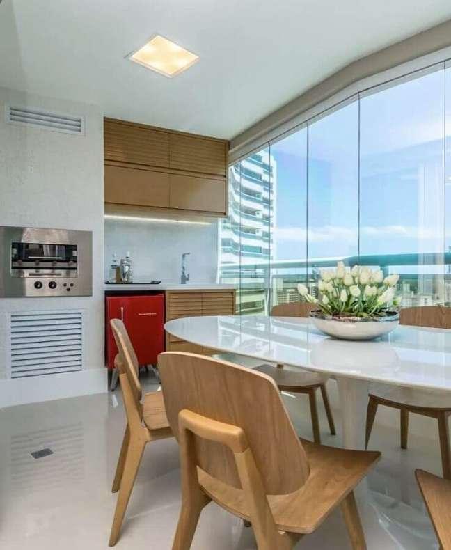 11. Apartamento com varanda gourmet decorada com cadeiras e armários de madeira – Foto: Homify
