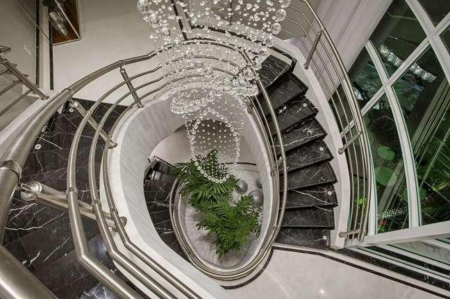 22. O lustre para escada alta se aproxima do jardim de inverno do imóvel. Projeto de Aquiles Nicolas Kílaris