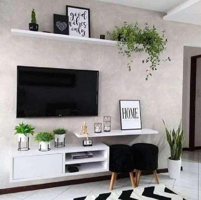 54. Sala de TV decorada com puff banqueta preto e parede de cimento queimado – Foto: Fashion Bubbles