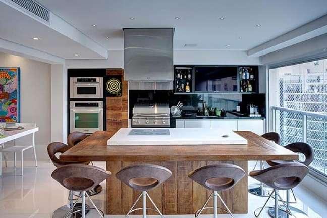 42. Ilha planejada com cooktop para decoração de apartamento com varanda gourmet moderna – Foto: Pinterest
