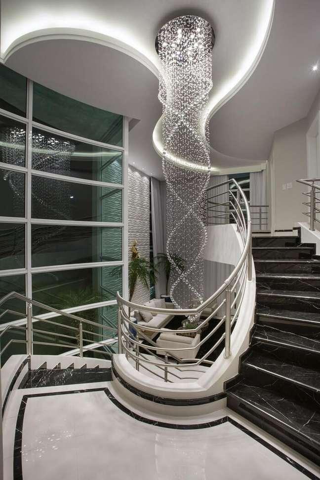 4. O lustre comprido para escada se destaca na decoração do ambiente. Projeto de Aquiles Nicolas Kílaris