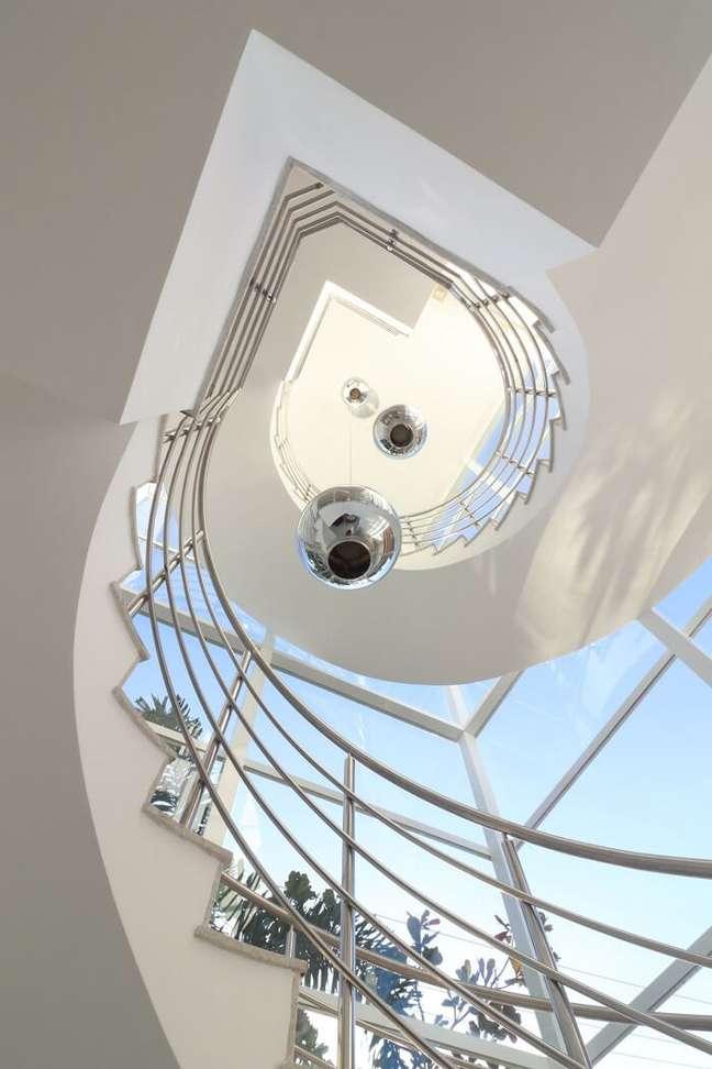 25. Modelo de lustre para escada pé direito alto metálico. Projeto de RAWI Arquitetura + Design
