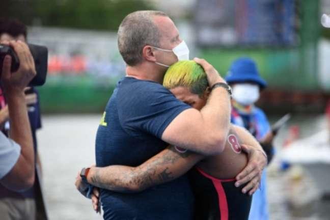 Abraço de Ana Marcela no treinador Fernando Possenti (Foto: OLI SCARFF / AFP)