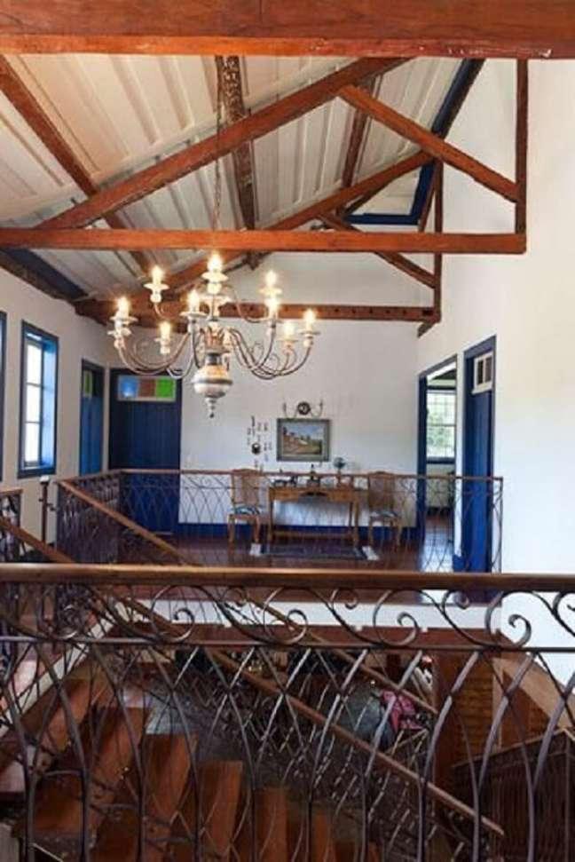20. O lustre para escada candelabro é perfeito para complementar a decoração de casa de campo. Projeto de Maria do Carmo Ferraz