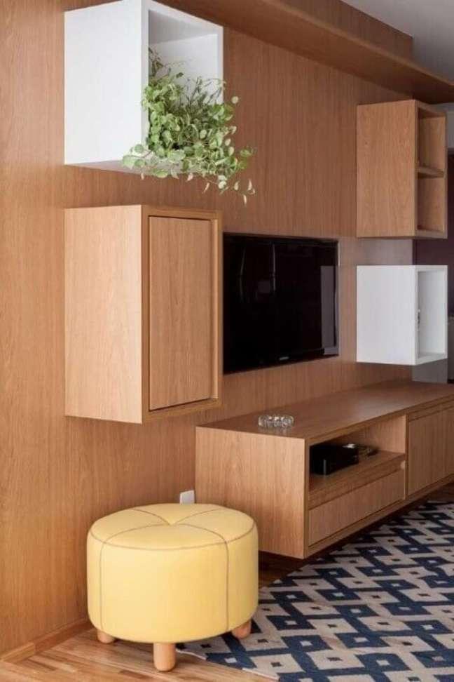 21. Decoração com puff banqueta para sala de TV com estante planejada de madeira – Foto: Tria Arquitetura