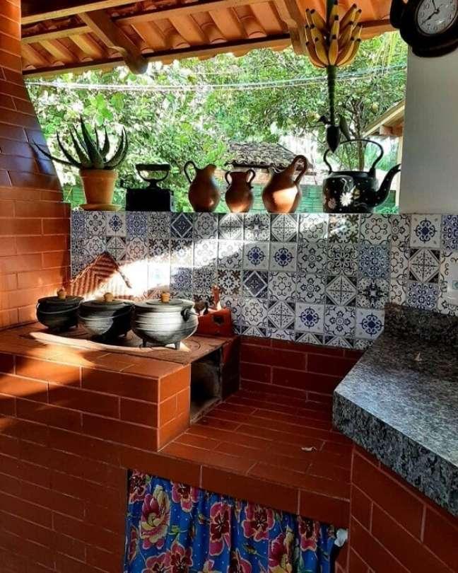 10. Área gourmet com churrasqueira e fogão a lenha revestidos de tijolinho e cortina para armários – Foto Giselma Teixeira