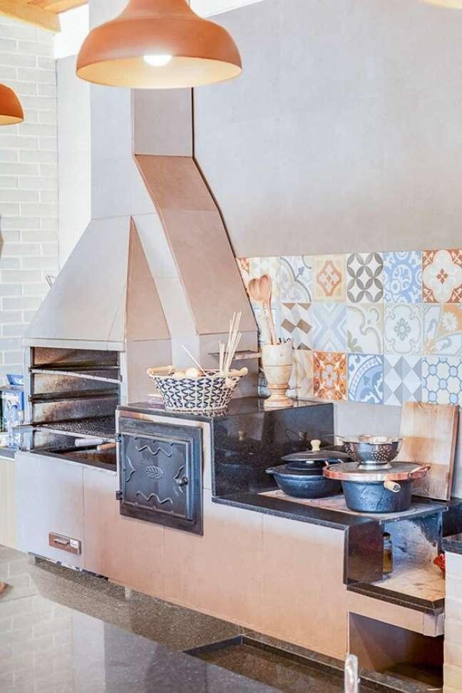 3. Área gourmet com churrasqueira e fogão a lenha ao lado e parede com revestimento colorido – Foto Archtrends