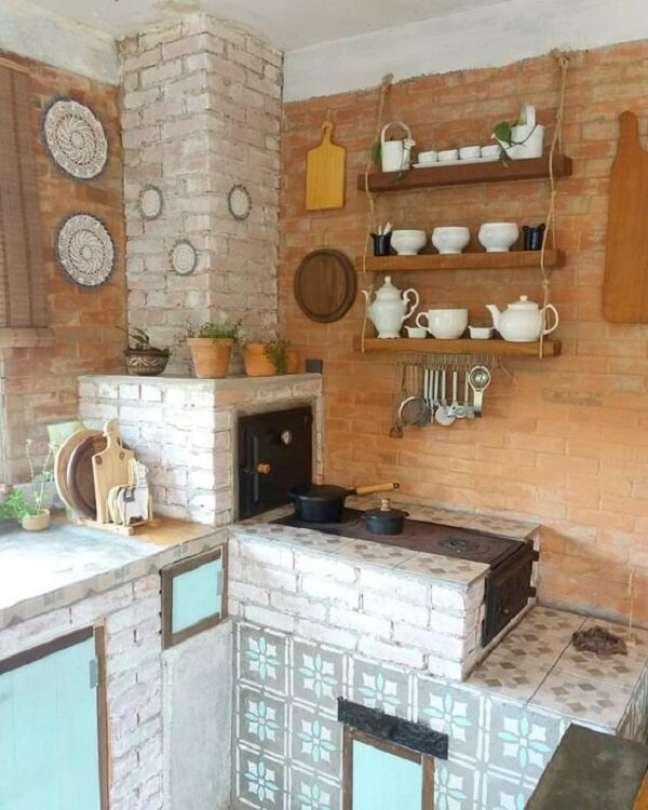 22. Área gourmet com fogão a lenha e prateleiras acima para organizar os itens da cozinha – Foto Arkpad