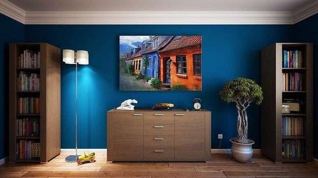 1. Móveis de madeira para decoração de sala com parede azul – Foto: Pixabay