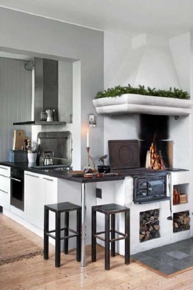 32. Área gourmet moderna com fogão a lenha e moveis planejados ao lado – Foto Pinterest